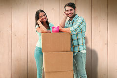 Composite image of happy young couple with moving boxes and piggy bank Stock Photos