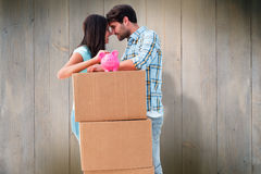 Composite image of happy young couple with moving boxes and piggy bank. Happy young couple with moving boxes and piggy bank against wooden planks Royalty Free Stock Photos