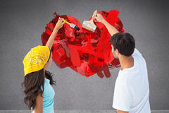 Composite image of happy young couple painting together Stock Photo