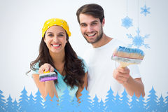 Composite image of happy young couple painting together Royalty Free Stock Photography