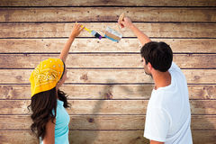 Composite image of happy young couple painting together Stock Photos