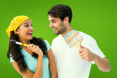 Composite image of happy young couple painting together and laughing Stock Photo