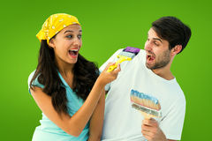 Composite image of happy young couple painting together and laughing Stock Photography