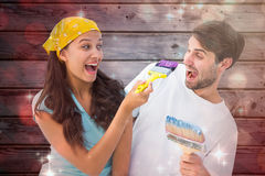 Composite image of happy young couple painting together and laughing Royalty Free Stock Photography