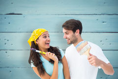 Composite image of happy young couple painting together and laughing Stock Images