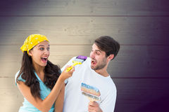 Composite image of happy young couple painting together and laughing Stock Image