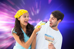 Composite image of happy young couple painting together and laughing Royalty Free Stock Photos