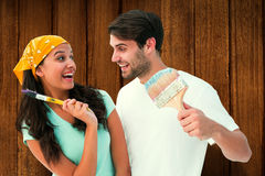 Composite image of happy young couple painting together and laughing Royalty Free Stock Images