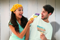 Composite image of happy young couple painting together and laughing Stock Photos