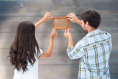Composite image of happy young couple putting up picture frame Stock Images