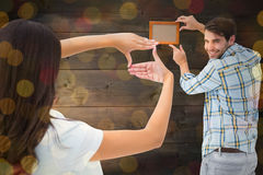 Composite image of happy young couple putting up picture frame Royalty Free Stock Images