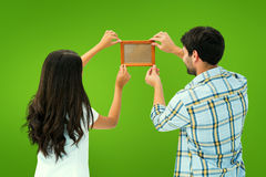 Composite image of happy young couple putting up picture frame Stock Photos