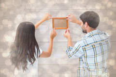 Composite image of happy young couple putting up picture frame Stock Image