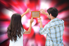 Composite image of happy young couple putting up picture frame Royalty Free Stock Image