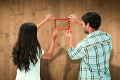 Composite image of happy young couple putting up picture frame Stock Photography