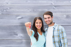 Composite image of happy young couple showing new house key. Happy young couple showing new house key against bleached wooden planks background Stock Images