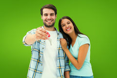 Composite image of happy young couple showing new house key Stock Images