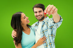 Composite image of happy young couple showing new house key Royalty Free Stock Images