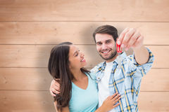 Composite image of happy young couple showing new house key Stock Photo
