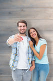 Composite image of happy young couple showing new house key. Happy young couple showing new house key against pale grey wooden planks Royalty Free Stock Images