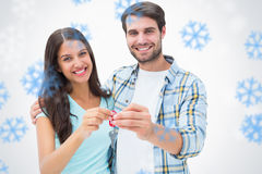 Composite image of happy young couple showing new house key Stock Image
