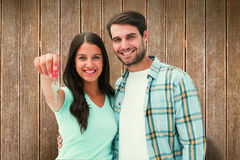 Composite image of happy young couple showing new house key. Happy young couple showing new house key against wooden planks Stock Images