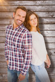 Composite image of happy young couple standing back to back Royalty Free Stock Photo