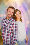 Composite image of happy young couple standing back to back Stock Photography
