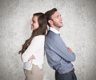 Composite image of happy young couple standing back to back Stock Image