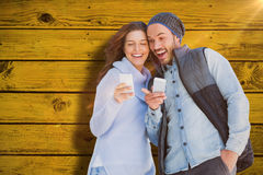 Composite image of happy young couple using mobile phone. Happy young couple using mobile phone against green paint splashed surface Stock Photos
