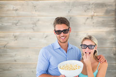 Composite image of happy young couple wearing 3d glasses eating popcorn Royalty Free Stock Image