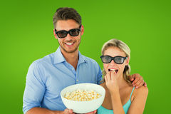 Composite image of happy young couple wearing 3d glasses eating popcorn Royalty Free Stock Photo