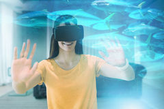 Composite image of happy young woman gesturing while using virtual reality glasses Stock Photos