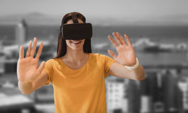 Composite image of happy young woman gesturing while using virtual reality glasses Stock Photo