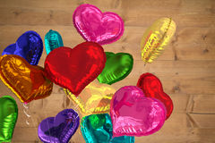 Composite image of heart balloons. Heart balloons against bleached wooden planks background Stock Photo