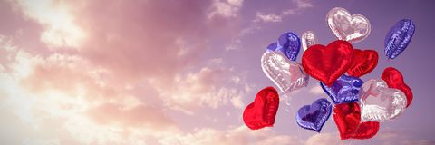 Composite image of heart balloons. Heart balloons against cloudy sky landscape Stock Photo