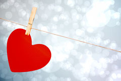 Composite image of heart hanging on line Stock Photos