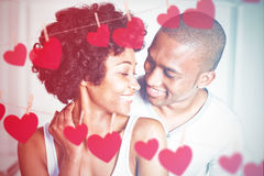 Composite image of hearts hanging on a line. Hearts hanging on a line against close up of couple at home Royalty Free Stock Image