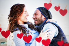 Composite image of hearts hanging on a line. Hearts hanging on a line against closeup of cheerful couple Stock Photo