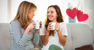 Composite image of hearts hanging on a line. Hearts hanging on a line against mother and daughter drinking tea Stock Image