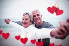 Composite image of hearts hanging on a line. Hearts hanging on a line against portrait of happy senior couple with arms outstretched Stock Images