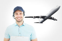 Composite image of hhappy male courier man wearing headset Stock Image