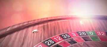 Composite image of high angle view of ball on 3d wooden roulette wheel Royalty Free Stock Photos
