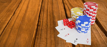 Composite image of high angle view of casino tokens with playing cards and dice Stock Images