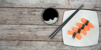 Composite image of high angle view of chopstick by salmon sushi in plate Stock Photography