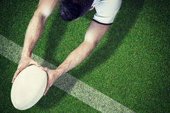 Composite image of high angle view of man holding rugby ball with both hands stock photo