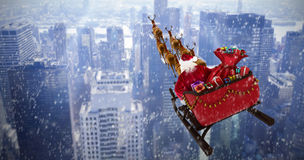 Composite image of high angle view of santa claus riding on sled during christmas Royalty Free Stock Photography