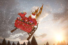 Composite image of high angle view of santa claus riding on sled during christmas Stock Images