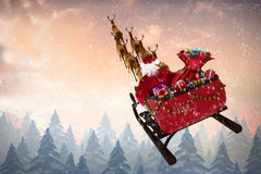 Composite image of high angle view of santa claus riding on sled during christmas Royalty Free Stock Photo