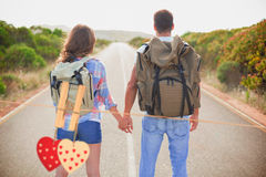 Composite image of hiking couple standing on countryside road Stock Image